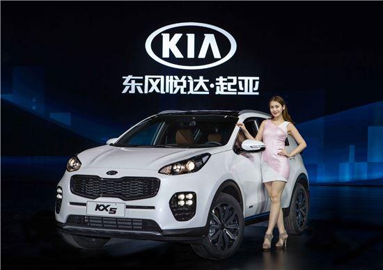 10일(현지시간) 중국 충칭 엑스포센터에서 열린 기아자동차 '중국형 신형 스포티지(KX5)' 출시 행사에서 홍보모델이 차량과 기념촬영을 하고 있다.