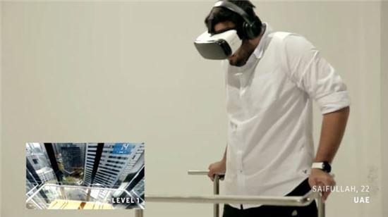 삼성전자 VR 치료 실험 `Be Fearless` 참가자가 HMD `기어VR`을 착용해 가상 환경을 통해 고소공포증을 치료하고 있다. 왼쪽 하단 작은 화면이 VR에서 보여지는 가상 환경.