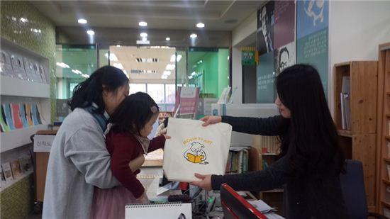 용인시가 북스타트 운동 일환으로 나눠주는 책 꾸러미를 학부모와 유아가 받고 있다.