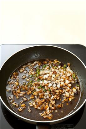 4. 냄비에 식용유를 두르고 마른고추, 양파, 풋고추, 표고버섯을 넣어 볶다가 분량의 깐풍 소스를 넣고 끓여 끓으면 튀긴 가지를 넣어 섞는다.