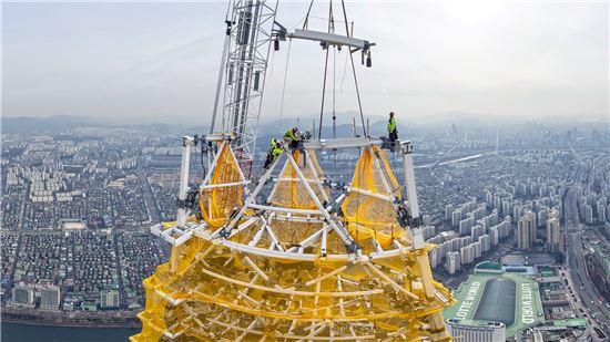 롯데월드타워 최상층부에서 64톤급 타워크레인을 활용한 다이아그리드 랜턴 설치 작업이 진행되고 있다.(자료:롯데건설)