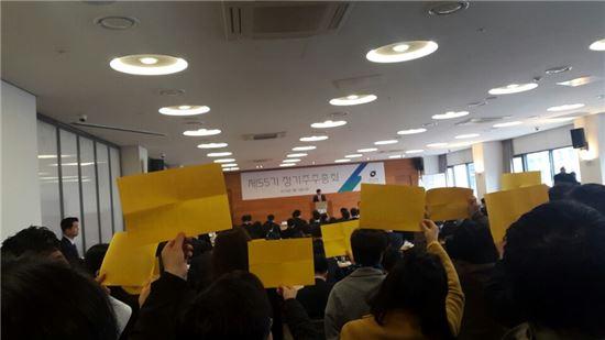 18일 대신증권 제55기 정기주주총회에서 나재철 대표가 안건을 상정하고 있는 가운데 이를 반대하는 일부 주주들이 오너일가 경영을 반대한다는 내용의 노란 종이를 들고 항의하고 있다.