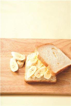 2. 식빵은 가운데에 칼집을 넣어 주머니처럼 만들고 썬 바나나를 넣는다.