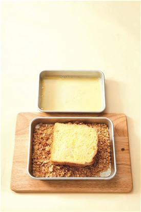 3.우유와 달걀을 잘 섞어 설탕과 소금을 넣어 녹인다. 식빵에 우유 달걀물을 앞뒤로 골고루 묻힌 후 콘프레이크를 묻힌다. (Tip 콘프레이크는 비닐봉지에 넣어 약간만 부스러뜨려서 묻히면 더 잘 붙는다.)