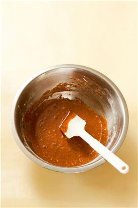2. 달걀노른자에 설탕 25g을 넣어 미색이 돌 때까지 잘 저어 박력분과 옥수수가루를 체에 쳐서 넣고 잘 섞은 다음 녹인 초콜릿을 넣는다.