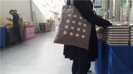 한 학생이 이대 기념품 가방을 메고 있다.