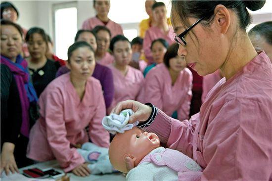 지난해 12월 11일(현지시간) 중국 베이징(北京)의 출산 도우미 인력 송출 업체 리밍에서 도우미 여성들이 실물 크기의 아기 인형으로 아기 돌봄 요령을 배우고 있다. 그러나 '한 자녀 정책'이 공식 폐지된 올해 들어 출산 도우미 수요가 폭증하자 가사 도우미들이 교육ㆍ훈련조차 제대로 받지 않은 상태에서 출산 도우미로 변신하는 일까지 벌어지고 있다. 베이징(중국)=AP연합뉴스