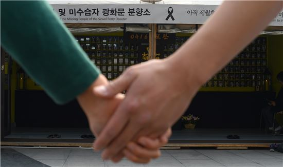세월호 2주기를 앞둔 12일 서울 광화문광장에 마련된 희생자 분향소에서 두 학생이 헌화를 하기 전에 손을 맞잡고 있다. 사진=윤동주 기자 doso7@