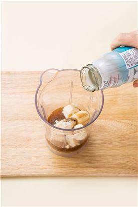 2. 믹서에 얼린 바나나, 에스프레소, 카다몬, 코코넛 워터, 아몬드가루를 넣어 곱게 갈아 잔에 담는다. (Tip 코코넛 워터가 없으면 탄산수나 생수를 이용한다.)