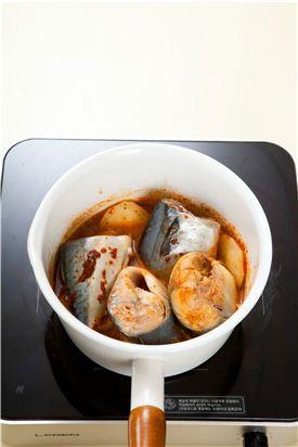 4. 냄비에 감자를 넣고 고등어, 양파, 풋고추, 홍고추를 넣고 조림장을 넣어 자작하게 끓이다가 대파를 넣는다.