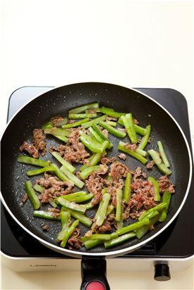 3. 팬을 달구어 기름을 두르고 쇠고기를 볶다가 어느 정도 익으면 오이를 넣어 볶는다.