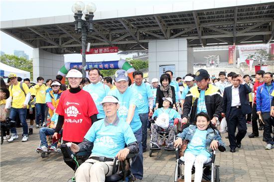 박홍섭 마포구청장이 2016 마포 거북이 마라톤 행사에 참석, 장애인 휠체어를 밀고 있다.
