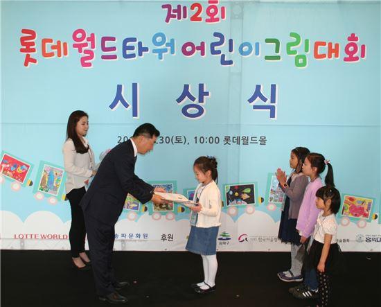 박현철 롯데물산 사업총괄본부장이 롯데월드타워 어린이 그림대회 상장과 장학금을 수상자에게 수여하고 있다.