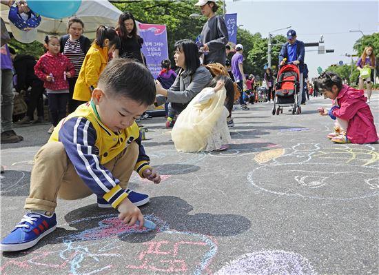 한 어린이가 도로 한 복판에서 그림을 그리고 있다.