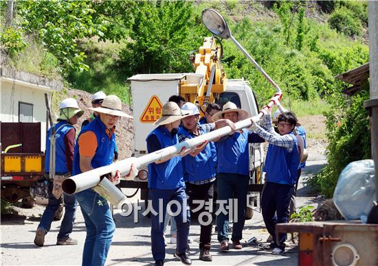 ▲지난12일 삼성전자 임직원들이 무주 호롱불 마을에서 노후 보안등을 수거하고 있다. (제공=삼성전자)