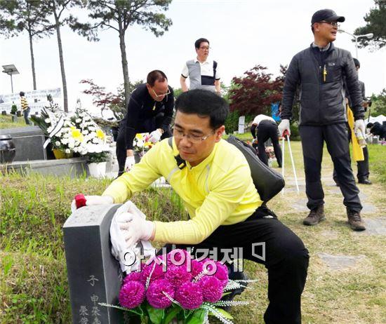 김경진 당선인 선거 자원봉사자들이 15일 망월동 5·18 구 묘역에서 청소를 하고 있다.