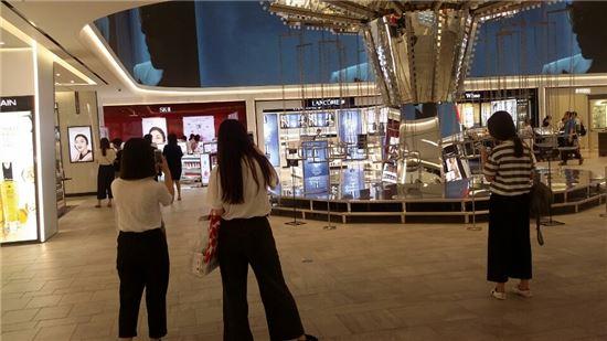 """▲지난 22일 신세계면세점 10층에 있는 '회전목마' 작품 앞에서 중국인관광객들이 기념사진을 찍고 있다. 이들은 매장에 들어서자마자 """"와-!""""하고 감탄사를 내뱉었다."""