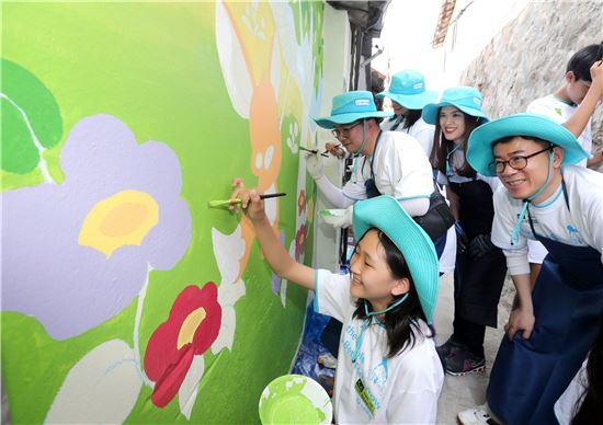 대우건설 임직원과 가족들이 성동구 마장동에서 환경개선을 위해 건물에 벽화를 그리고 있다.