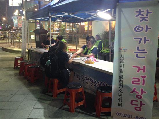 25일 밤 9시 서울 관악구 신림역 앞에서 금천청소년쉼터 활동가들이 청소년들과 상담을 진행하고 있다.