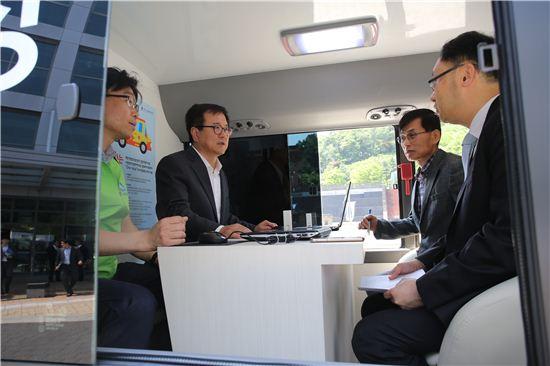 경기신보가 찾아가는 현장보증 서비스 활성화를 위해 도입한 전용버스에서 서포터즈들이 고객과 보증지원 상담을 하고 있다.