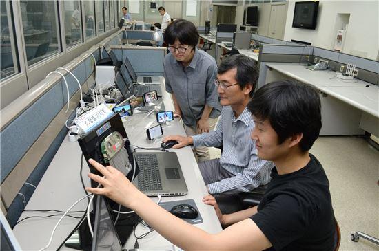 ETRI 박도현 연구원(맨앞), 신연승 책임연구원, 오현주 책임연구원(우측에서 좌로 순서)이 소형셀 기지국 SW기술을 이용해 동영상 전송을 시연하고 있는 모습.(사진=ETRI)