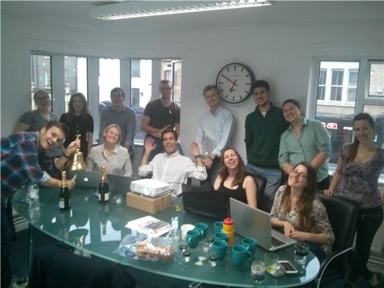 신디케이트룸 직원들이 자금모집을 성공적으로 마친 후 회의실에 모여 이를 축하하고 있다.