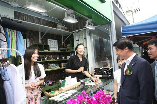 이해식 강동구청장이 명일전통시장 청춘마켓 개장식에 참석한 후 매장을 둘러보며 상인들과 인사를 나누고 있다.