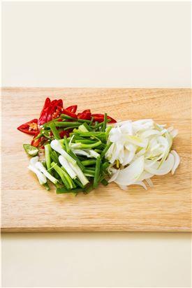 2. 양파는 채 썰고 실파는 먹기 좋은 크기로 썰고 홍고추와 풋고추는 반으로 갈라 어슷하게 썬다.
