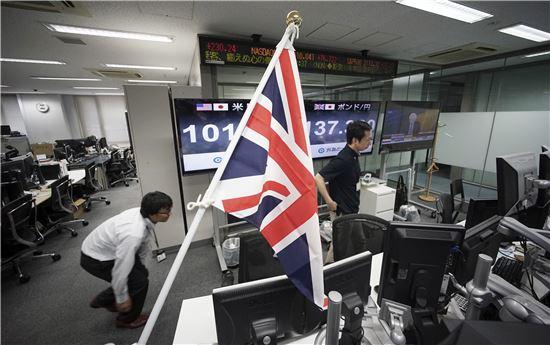 ▲도쿄의 한 증권회사에서 영국 국기를 걸어놓고 있다. 24일 장중 한때 엔화가치는 달러당 99엔까지 급등했다. (AP = 연합뉴스)