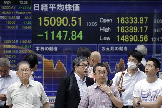 지난 24일 일본 도쿄에서 시민들이 브렉시트 여파로 8% 가까이 급락한 증시 상황을 보여주는 전광판 앞을 지나고 있다(EPA=연합뉴스)