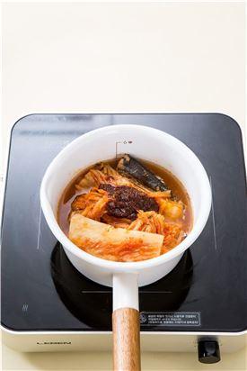 4. 냄비에 꽁치와 묵은지를 넣고 조림장을 넣어 20분 정도 끓이다가 양파, 청양고추, 대파를 넣어 자작하게 끓인다.