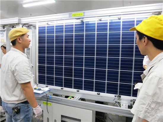 한화큐셀 태양광 모듈 공장 직원들이 60셀 모듈 완제품을 최종 검수하고 있다.