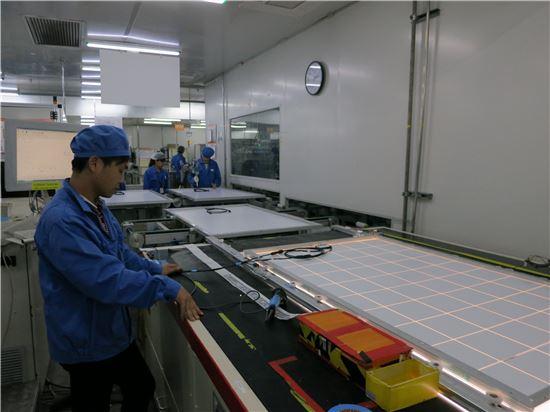 한화큐셀 태양광 모듈 공장 직원들이 60셀 모듈 제품을 검수하고 있다.