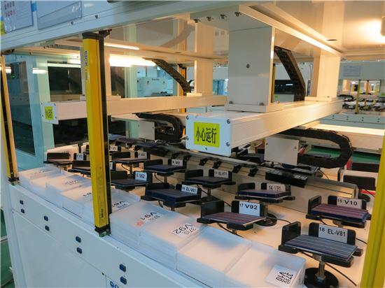태양광 셀 공장의 로보트 팔이 생산된 셀을 효율에 따라 자동 분류하고 있다.