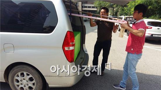 장현우군 아버지가 장군의 졸업사진 소품을 승합차에서 꺼내고 있다. 길이 약 2M짜리 소품을 운반하기 위해 장군 아버지는 승합차를 빌렸다. 사진=장현우군 제공