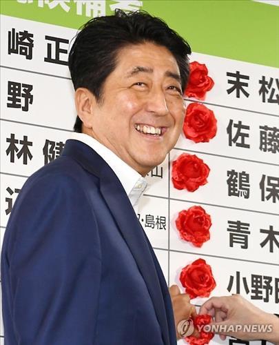 아베 신조(安倍晋三) 일본 총리가 10일 치러진 참의원 선거후 도쿄의 자민당사에서 당선이 확정된 자민당 의원들의 이름 옆에 꽃을 붙이고 있다. 사진=연합뉴스