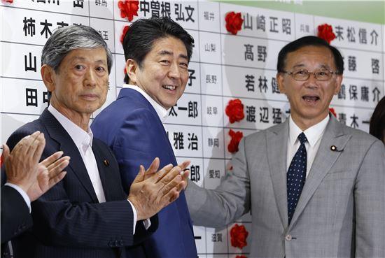 ▲아베 신조 일본 총리(가운데)가 10일 참의원 선거결과를 보며 기쁨의 미소를 짓고 있다. (AP = 연합뉴스)