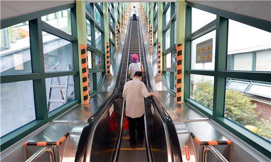 동대문구 주민들이 신이문역 3번 출구에 새로 설치된 에스컬레이터를 이용하고 있다.