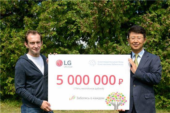 LG전자 CIS지역 기획관리담당 한재동 상무(오른쪽)가 러시아 유명 배우이자 하벤스키 재단을 운영하고 있는 콘스탄틴 하벤스키(왼쪽)에게 후원금을 전달하고 있다.