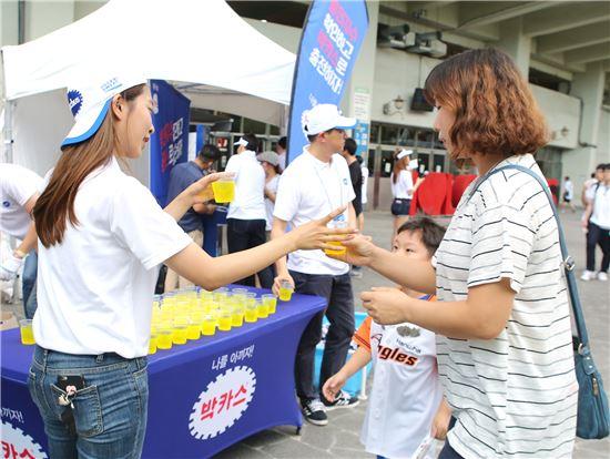 지난 14일 잠실야구장에서 진행된 동아제약 박카스 샘플링 행사에서 야구장을 찾은 사람들에게 컵에 박카스와 얼음을 넣어 나눠주고 있다.