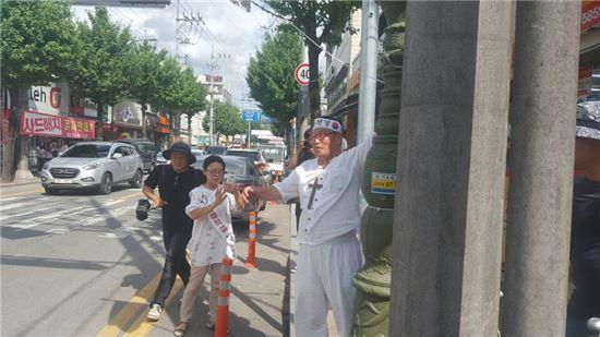 ▲이석인 대한진리당 총재(오른쪽)가 현수막을 걸던 도중 성주군민들과 충돌하고 있다.