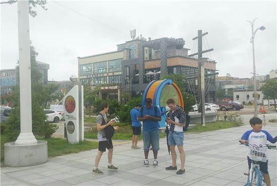 외국인들이 속초 엑스포 공원에서 포켓몬 고 게임을 즐기고 있다.