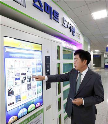 정찬민 용인시장이 기흥역 무인 스마트 도서관을 찾아 책 대출 시연을 하고 있다.