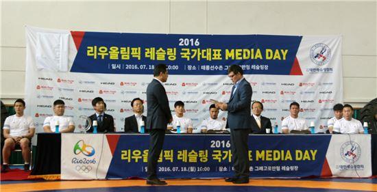 18일 이재호 맘스터치 부사장이 김영남 대한레슬링협회장에게 감사패를 전달 받고 있다.