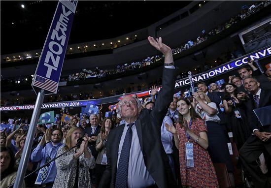 미국 민주당 전당대회 이틀째인 26일(현지시간) 대통령 후보 경선에서 막판까지 경합을 벌였던 버니 샌더스 상원의원이 힐러리 클린턴 전 국무장관을 대선 후보로 선언하기 위해 단상으로 이동하며 대의원들에게 손을 흔들고 있다. 이날 민주당은 클린턴을 대선 후보로 정식 지명했다.(사진=EPA연합)