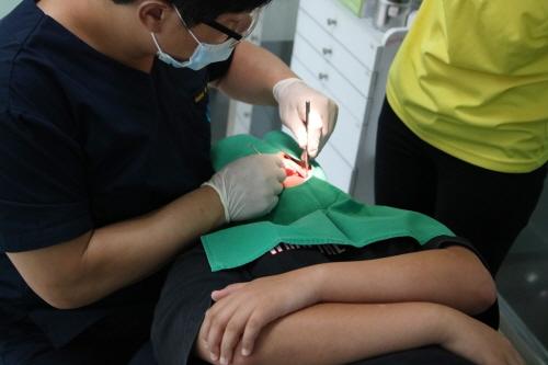 유디치과의 '우리동네 이 밝은 세상' 대상자로 선정된 최모군(15세)이 충치치료를 받고 있다.