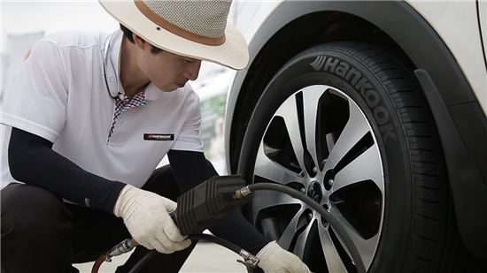 한국타이어 서비스 직원이 고객 차량의 타이어를 점검하고 있다.