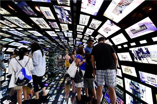 삼성 837에서 관람객들이 다양한 크기의 갤럭시 스마트폰과 태블릿으로 구성된 '소셜 갤럭시'를 체험하고 있다.