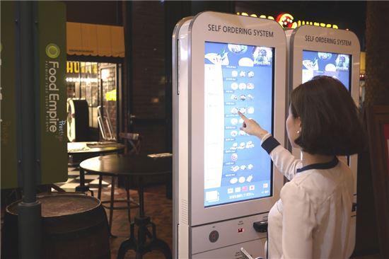 서울 여의도 푸드엠파이어 IFC몰점에서 한 고객이 키오스크를 이용해 메뉴를 주문하고 있다.