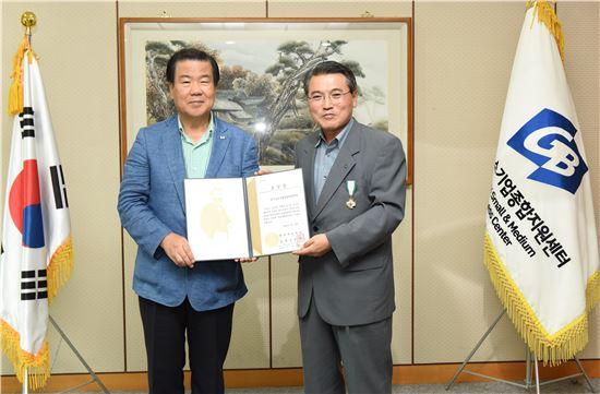 윤종일 경기중기센터 대표(오른쪽)가 김훈동 대한적십자사 경기도지회 회장으로부터 금장을 받은 뒤 기념촬영을 하고 있다.
